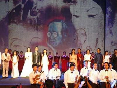Dàn nhạc giao hưởng cùng các ca sĩ chào khán giả sau bài Đóa hoa vô thường - phông nền sân khấu là slide những bức tranh của TCS